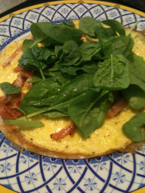 Close up of omelette with spinach, bacon and cheese