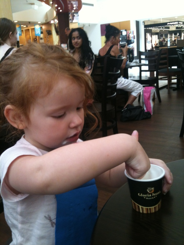Two and a half year old niece with her hand in her babycino